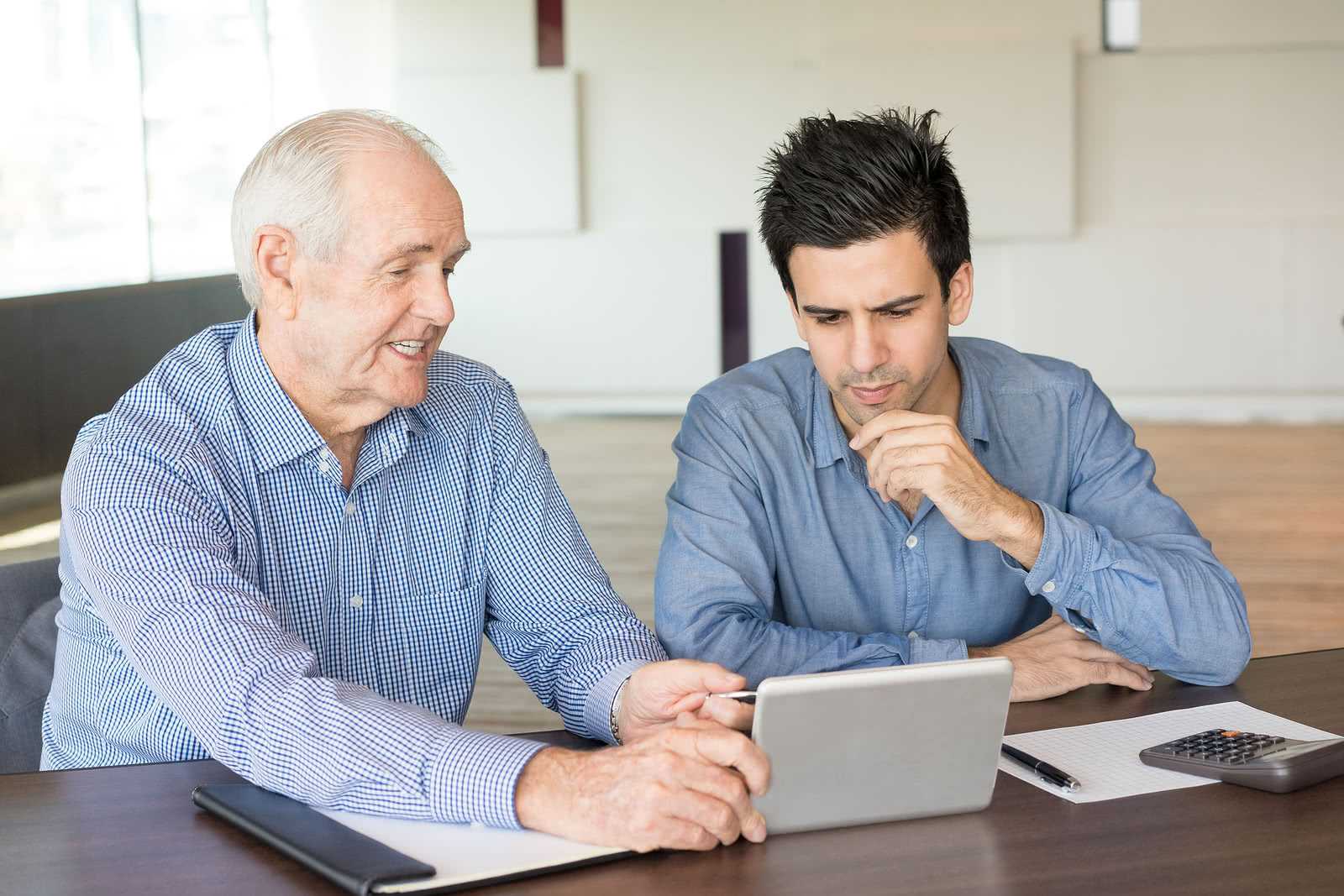 Senior business owner showing younger owner his small business network