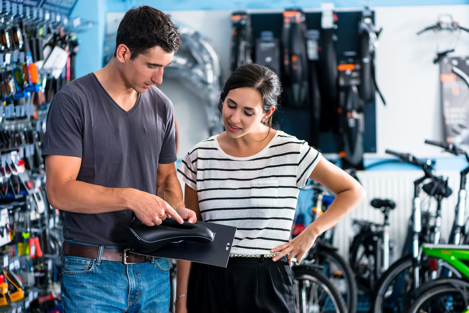 Male bike shop employee shows bike parts to a female customer