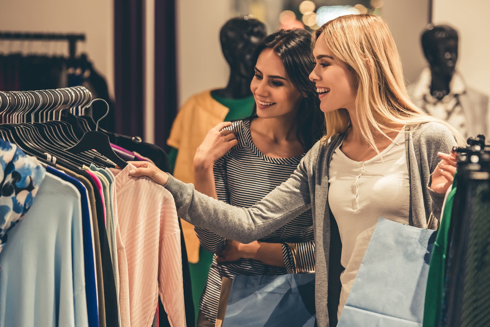 Two women shopping for clothes thinking about starting a retail business