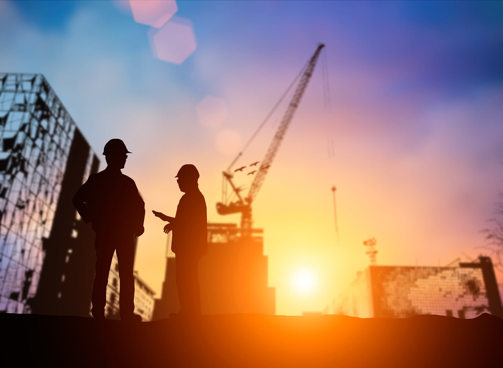 Two construction workers stand in front of a crane with sunset background