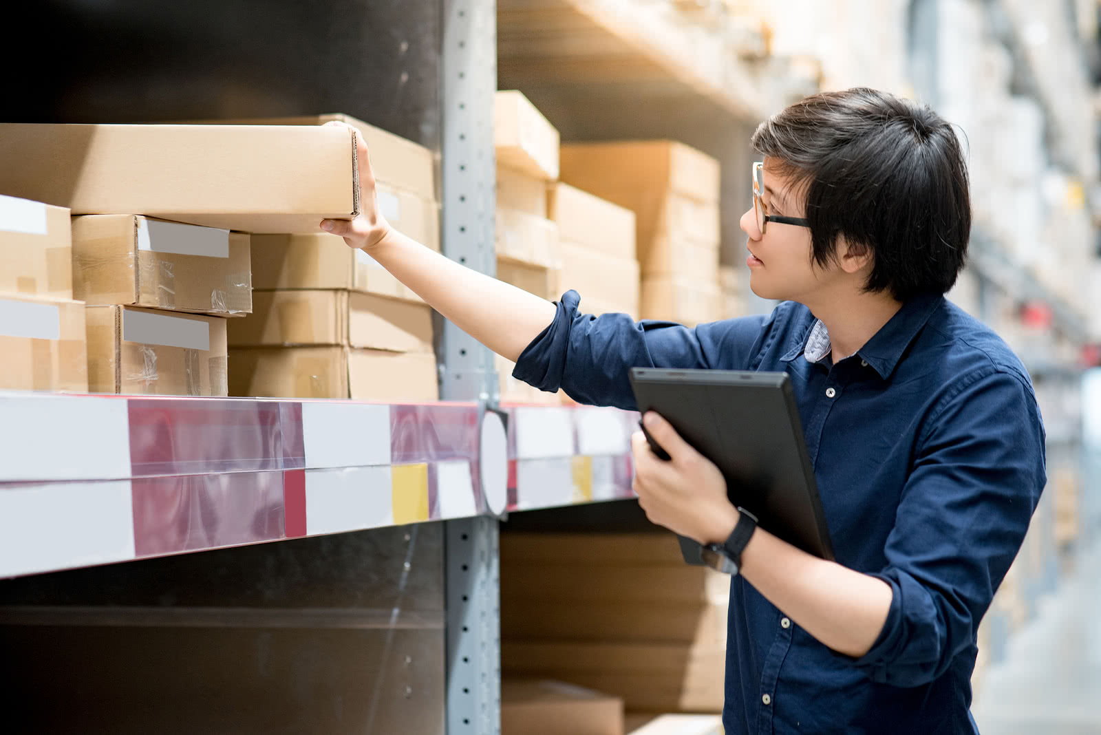 A business owner tracks inventory, a key part of inventory management for small business