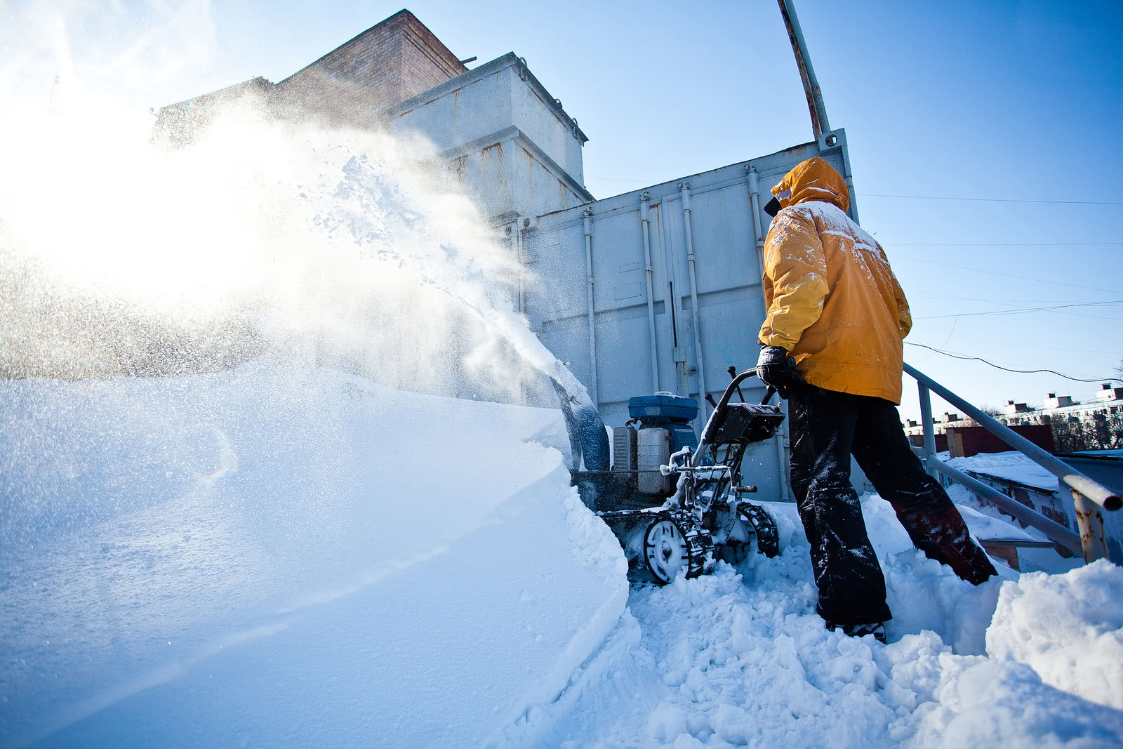 A seasonal worker plows snow for a landscape company