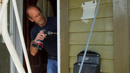 An employee repairs a residential home