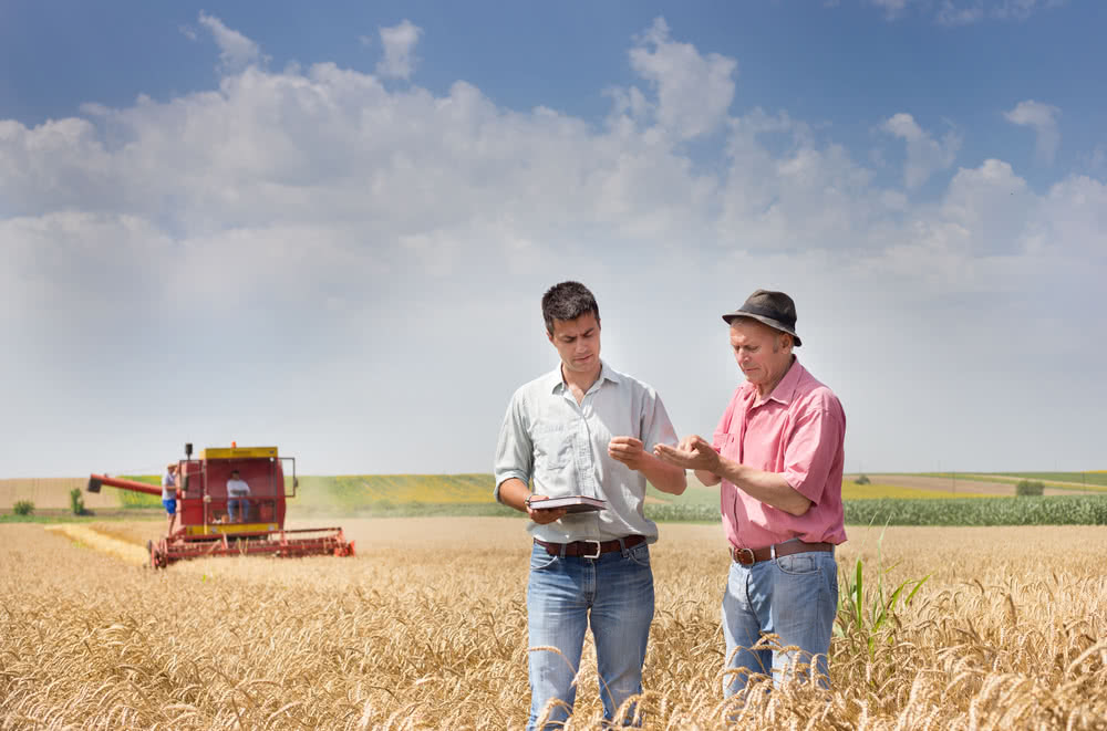 Two farmers in a field discuss offering a new service after a business loss