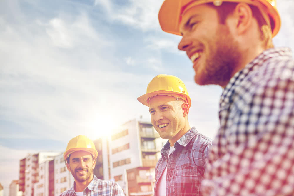 Three construction workers on-site discussing cost control in construction managmenet