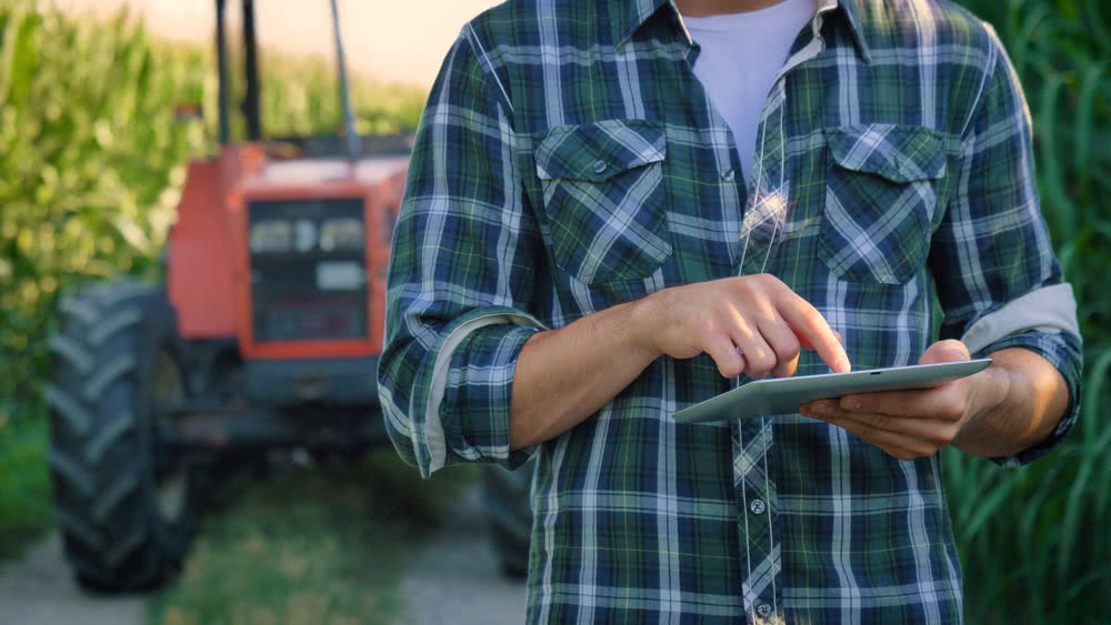 A farmer researches commercial loans on tablet as a way to purchase new equipment