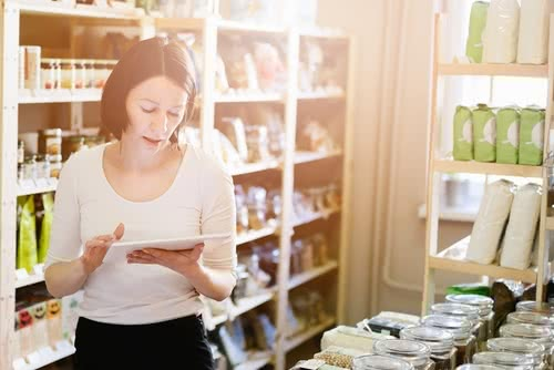 Female owner of local grocery store researching business loans for women with bad credit on tablet