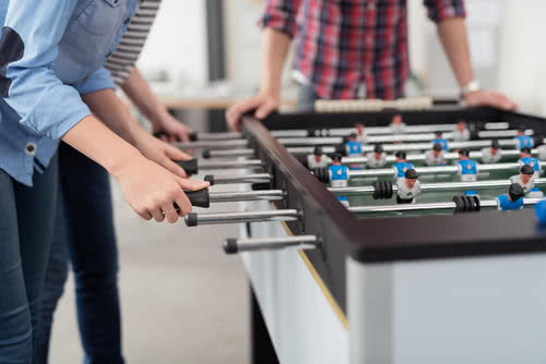 A few coworkers playing foosball on Employee Appreciation Day