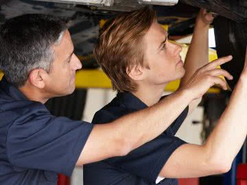 Auto shop owner trains new mechanic, providing the benefits of training to employees