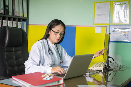 Health clinic owner keeps track of employee hours on laptop