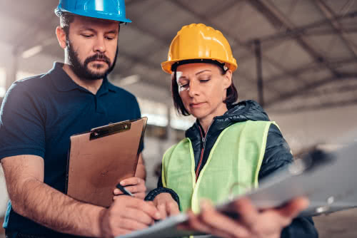 Two construction workers review small business tips and advice