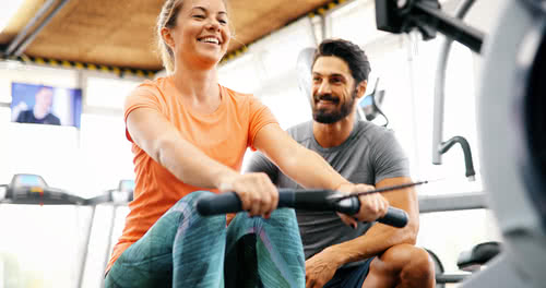 Woman works with personal trainer on new equipment at the gym