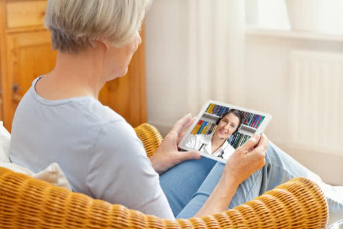 Doctor consults with elderly patient through telemedicine software