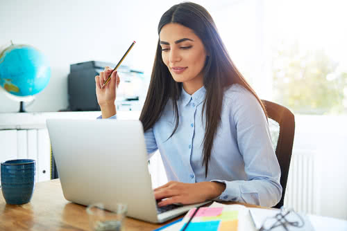 Woman business owner reads her business plan on her laptop