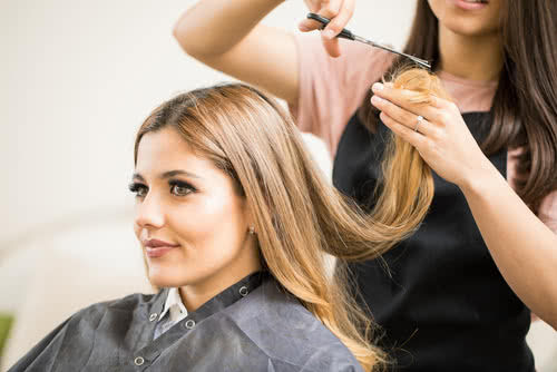 Portrait of a gorgeous young blonde getting her hair cut by a hairstylist at a beauty salon
