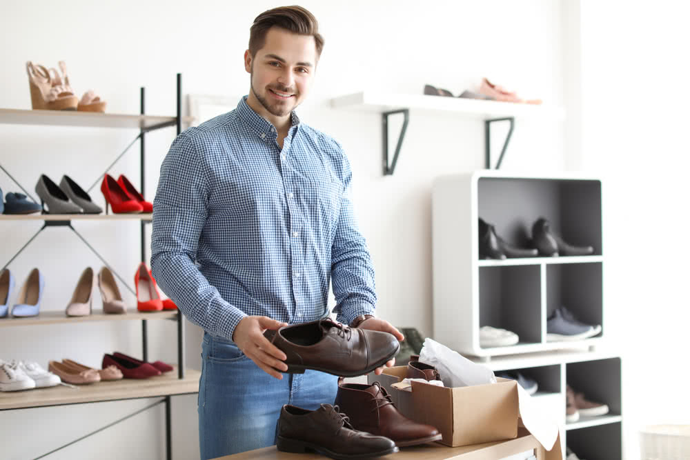 Young man choosing shoes in store - net income vs. net revenue