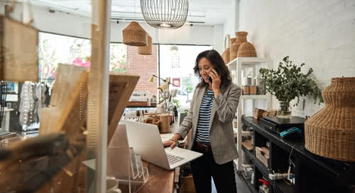 Smiling young woman standing behind a counter in her stylish boutique working on a laptop and talking on a cellphone