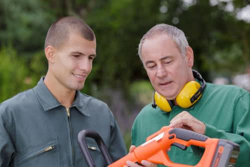 gardeners looking at lawnmower machine