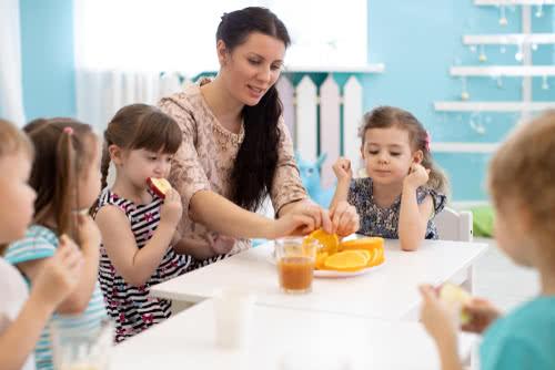 Children and carer together eating fruits in kindergarten or daycare