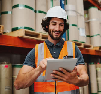 Male warehouse manager adding stock inventory data in digital tablet in warehouse wearing a white hardhat and safety vest standing