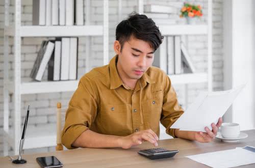 Man at desk calculating owner